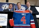 Edmonton Oilers general manager Steve Tambellini, left, holds up a jersey with draft pick Taylor Hall, center, and Kevin Lowe, the NHL team